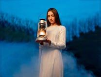 神奇神秘的女孩在有一盏煤油灯的一个黑暗的夜森林里在她的手上 免版税库存图片