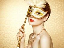 神奇金黄威尼斯式面具的美丽的少妇 库存图片