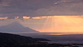 神的光、风雨如磐的天空和日出在一个风景在圣徒山Athos附近 免版税库存照片