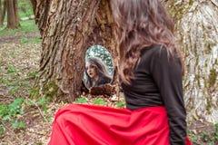 神秘的妇女在镜子看 免版税库存图片