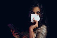 神秘的美丽的女孩,盖面孔用卡片和拿着片剂手中,网上啤牌概念 免版税图库摄影