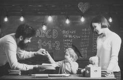 神童和天才概念 父母要长大天才儿子 神童父亲,老师阅读书,教学 免版税库存照片