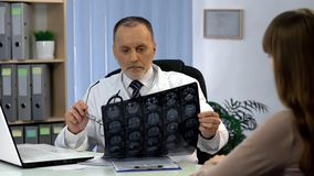 神经外科医师观察脑子X-射线,去告诉关于病魔的患者 免版税图库摄影