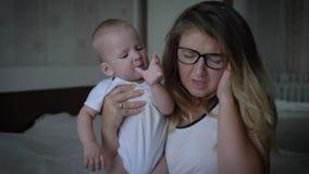 神经衰弱,有头疼的紧张的年轻母亲拿着在手上的婴儿坐床 影视素材
