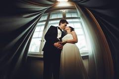 神色从下面在站立在t之间的一对亲吻的婚礼夫妇 库存照片