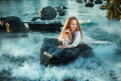 神仙在一块石头在水中说谎 免版税库存照片