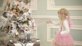 神仙服装的小女孩有桃红色翼的迷惑圣诞树 影视素材