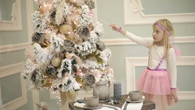 神仙服装的小女孩有桃红色翼的迷惑圣诞树 股票视频