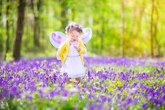 神仙的服装的小孩女孩在会开蓝色钟形花的草森林里 库存照片