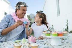 神仙的服装的敬酒茶的微笑的父亲和女儿 库存照片
