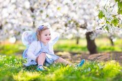 神仙的服装的逗人喜爱的小孩女孩在果子庭院里 免版税图库摄影