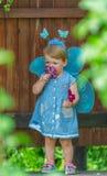 神仙的衣服的小女孩渴望与猩红色flore 免版税库存照片