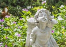 神仙的雕象在有花的庭院里 免版税库存图片