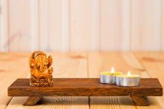 神Ganesha和一个蜡烛的木小雕象 库存照片