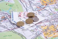 票和硬币在地图。 免版税图库摄影