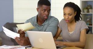 付票据付款的严肃的非裔美国人的夫妇网上 免版税库存照片