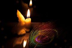 祷告和希望概念 与孔雀feathe的减速火箭的蜡烛光 库存照片