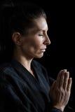 祷告姿势的女性空手道球员 免版税库存照片