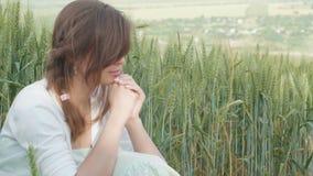 祷告的少女祈祷的词和看在领域,在谷物小尖峰中的一名妇女的天空享受自然的和比 股票视频