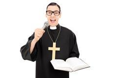 读祷告的男性教士在话筒 免版税库存照片