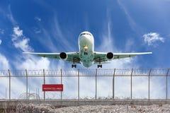 禁区篱芭和乘客飞机着陆美丽的b 免版税库存图片