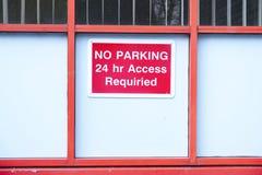 禁止停车24个小时通入标志红色和白色在木学校墙壁上 库存照片