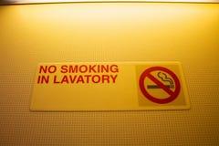 禁烟在洗手间在一间洗手间的标志警告在飞机 免版税库存照片