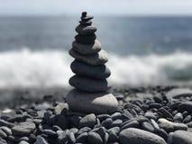 禅宗向海滩瑜伽凝思扔石头 免版税库存图片
