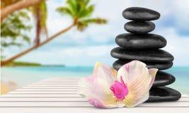 禅宗玄武岩石头和花在木桌上 免版税库存图片