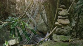 禅宗石平衡本质上在瀑布的安静的密林 与石堆的凝思场面,平衡,和谐的标志 股票视频