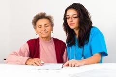 福利事业提供者帮助的老人 库存图片