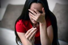 离婚概念 拿着定婚戒指的哀伤的孤独的妇女坐在内部家庭特写镜头 选择聚焦 库存图片