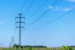 离开入距离的一定数量的高压杆与高压导线 库存照片