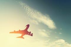 离开在日落的飞机。 免版税库存照片