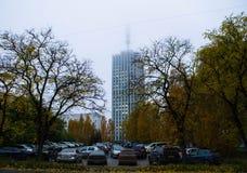 离开在雾的高大厦在黄色树背景  免版税库存照片