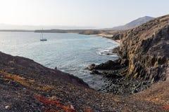 离开岩石海岸,兰萨罗特岛,加那利群岛的小船 免版税库存照片