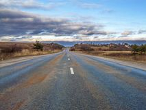 离开往天际的高速高速公路通过平的地形 免版税图库摄影