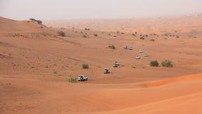 离开徒步旅行队打击通过阿拉伯沙丘的SUVs 免版税图库摄影