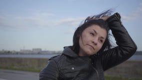 离开摩托车盔甲和调查照相机微笑的特写镜头的年轻女人 爱好,旅行和 股票录像