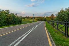 离开的沥青路线在城市公园在傍晚 免版税库存图片