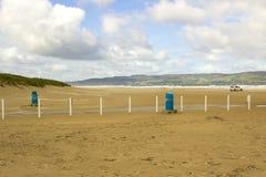 离开的海滩的金黄沙子在Benone的在爱尔兰的北海岸的伦敦德里郡 免版税库存照片