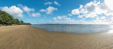离开的舒展海滩在一明亮的天 库存图片