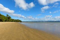 离开的舒展海滩在一明亮的天 库存照片
