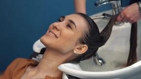 秀丽、护发和人概念-有美发师洗涤物头的愉快的年轻女人在美发店 股票录像