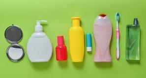 秀丽、自关心和卫生学的产品在绿色淡色背景 香波,香水,唇膏,阵雨胶凝体,牙刷 免版税库存照片