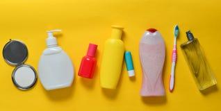 秀丽、自关心和卫生学的产品在黄色淡色背景 香波,香水,唇膏,阵雨胶凝体,牙刷 免版税库存照片