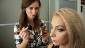 秀丽交谊厅化妆师绘在眼睛的阴影与刷子金发碧眼的女人妇女 影视素材