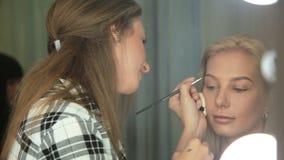 秀丽交谊厅化妆师绘有刷子的眼眉 白肤金发的妇女 股票录像
