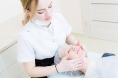 秀丽交谊厅 一名医疗美容师的特写镜头桃红色手套的做面孔按摩一名美丽的妇女 整容术 库存照片