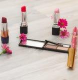 秀丽化妆桌,洗手间,与化妆瓶、唇膏和花 顶视图 免版税库存图片